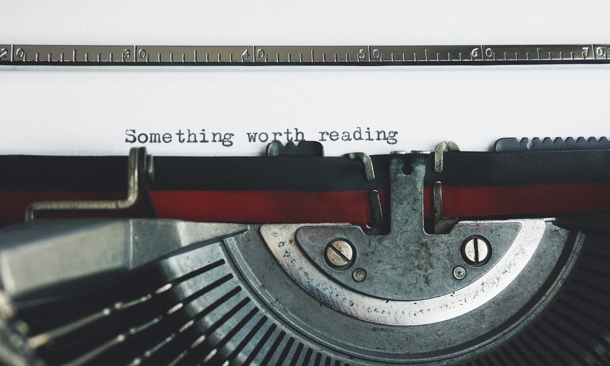 old-fashioned typewriter, traditional copywriting tool - shows the words: something worth reading - Suffolk copywriting - Suffolk copywriter